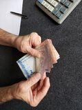H?nde eines ?lteren Mannes, der brasilianische Banknoten z?hlt stockbilder