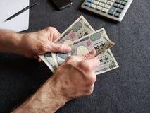 H?nde eines ?lteren Mannes, der japanische Banknoten h?lt stockbilder