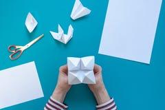H?nder av en ung flicka g?r pappers- konst av origami, p? en bl? bakgrund royaltyfri foto