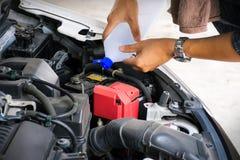 H?nder f?r arbetare f?r f?r man eller automatisk mekaniker tillfogar destillerat vatten till bilbatteriet Kontrollera och underh? royaltyfri fotografi