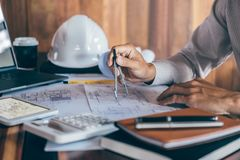 H?nder f?r konstruktionsteknik som eller arkitektarbetar p? ritningkontroll i arbetsplats, medan kontrollera informationsteckning arkivfoton