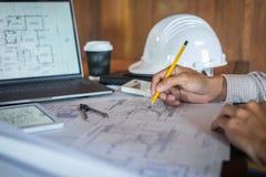 H?nder f?r konstruktionsteknik som eller arkitektarbetar p? ritningkontroll i arbetsplats, medan kontrollera informationsteckning fotografering för bildbyråer