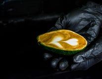 H?nder i svarta handskar och i dem en cappuccino med lattekonst i avokado Ovanlig kopp Nytt och h?rligt kaffe med mj?lkar royaltyfri foto