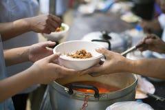 H?nderna av det rikt ger mat till h?nderna av det fattigt: Sociala problem av armod som hj?lps, genom att mata: Begreppsproblem a arkivfoto