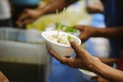 H?nderna av det rikt ger mat till h?nderna av det fattigt: Sociala problem av armod som hj?lps, genom att mata: Begreppsproblem a royaltyfri foto