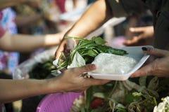 H?nderna av det rikt ger mat till h?nderna av det fattigt: Sociala problem av armod som hj?lps, genom att mata: Begreppsproblem a royaltyfria foton