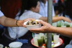 H?nderna av det rikt ger mat till h?nderna av det fattigt: Sociala problem av armod som hj?lps, genom att mata: Begreppsproblem a royaltyfri bild