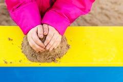 H?nderna av ett barn som spelar med sand arkivbild