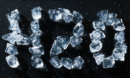 H2O water symbol written in ice cubes and melting. Water drops, all on a dark background Stock Photography