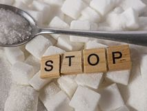H pile of white sugar cubes and stop word in block letters as advise on addiction calories excess and sweet unhealthy food abuse c. Conceptual still life with royalty free stock image