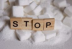 H pile of white sugar cubes and stop word in block letters as advise on addiction calories excess and sweet unhealthy food abuse c. Conceptual still life with stock photography