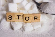 H pile of white sugar cubes and stop word in block letters as advise on addiction calories excess and sweet unhealthy food abuse c. Conceptual still life with stock images