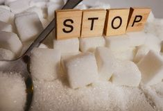 H pile of white sugar cubes and stop word in block letters as advise on addiction calories excess and sweet unhealthy food abuse c. Conceptual still life with stock photo
