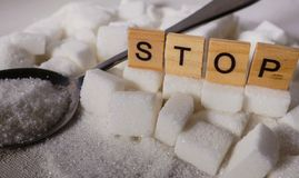 H pile of white sugar cubes and stop word in block letters as advise on addiction calories excess and sweet unhealthy food abuse c. Conceptual still life with stock image