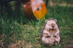 H?risson gai de jardin de d?coration en gros plan de figurine sur le fond vert de l'herbe et de la guitare photographie stock