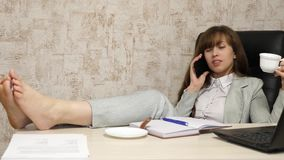 H?rlig aff?rskvinna som sitter i en f?t?lj med kal fot p? tabellen som vilar och dricker te, kaffe Flicka p? arbete arkivfilmer