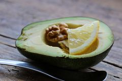 H?rlig avokado p? tr?bakgrund Begreppet av anv?ndbar mat Avokado med muttrar och en skiva av citronen och bredvid en sked royaltyfria bilder