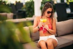 H?rlig b?rande baddr?kt f?r ung kvinna som dricker ett f?rgrikt coctailsammantr?de p? en kabin av strandklubbast?ngen bed?va arkivbilder
