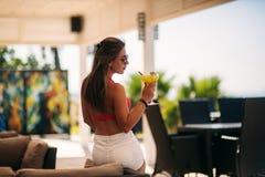 H?rlig b?rande baddr?kt f?r ung kvinna som dricker ett f?rgrikt coctailsammantr?de p? en kabin av strandklubbast?ngen bed?va royaltyfri foto