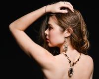H?rlig baksida av en ung kvinna med en halsband p? hennes nakna baksida royaltyfri foto