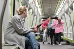 H?rlig blond kvinna som anv?nder den smarta telefonen, medan resa med tunnelbanakollektivtrafik arkivfoton
