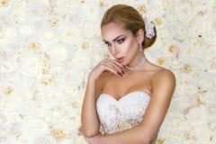 H?rlig brud i den vita br?llopskl?nningen p? bakgrunden av en v?gg av blommor - Bild fotografering för bildbyråer