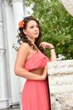 H?rlig brunett med lockigt h?r och den rosa kl?nningen royaltyfri fotografi