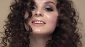 H?rlig brunettflicka med ett perfekt lockigt h?r och klassiskt smink som poserar i studion H?rlig le flicka stock video
