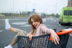 H?rlig flicka i sp?rvagnen n?ra supermarket utomhus- royaltyfri bild