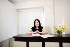 H?rlig flicka p? mottagandeskrivbordet som svarar appellen i tand- kontor royaltyfria bilder