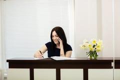 H?rlig flicka p? mottagandeskrivbordet som svarar appellen i tand- kontor royaltyfri fotografi