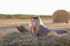 H?rlig flicka som l?ser en bok p? solnedg?ngen i en h?stack arkivfoto