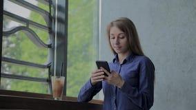 H?rlig flicka som sitter vid f?nstret med en telefon och en drink p? tabellen lager videofilmer