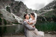 H?rlig gifta sig photosession Brudgummen cirklar hans unga brud, p? kusten av sj?n Morskie Oko poland royaltyfri foto