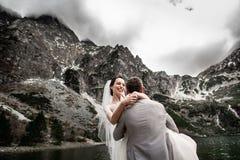 H?rlig gifta sig photosession Brudgummen cirklar hans unga brud, p? kusten av sj?n Morskie Oko poland arkivbild