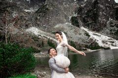 H?rlig gifta sig photosession Brudgummen cirklar hans unga brud, p? kusten av sj?n Morskie Oko poland arkivfoto