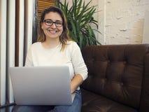 H?rlig kvinna f?r blandat lopp som sitter i en coffee shop genom att anv?nda hennes b?rbar dator royaltyfria bilder