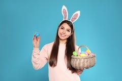 H?rlig kvinna i korg f?r innehav f?r kanin?rahuvudbindel med p?sk?gg arkivbild