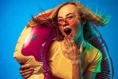 H?rlig kvinna i neonljus som isoleras p? bl? studiobakgrund fotografering för bildbyråer