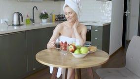 H?rlig kvinna med handduken p? huvudet som har en sunt frukost och kaffe lager videofilmer