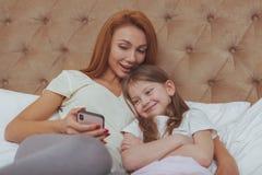 H?rlig kvinna och hennes lilla dotter som anv?nder den smarta telefonen royaltyfri fotografi