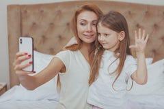 H?rlig kvinna och hennes lilla dotter som anv?nder den smarta telefonen arkivfoto