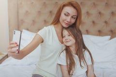 H?rlig kvinna och hennes lilla dotter som anv?nder den smarta telefonen royaltyfria bilder