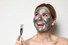 H?rlig kvinna som applicerar maskeringen p? framsida royaltyfri bild