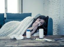 H?rlig kvinna som nyser att lida fr?n f?rkylning eller allergin som k?nner sig ligga himla p? soffan fotografering för bildbyråer