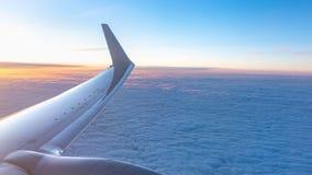H?rlig laxgryning och vingen av ett flygplan ovanf?r molnen arkivfoto