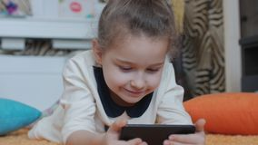 H?rlig liten flicka som spelar p? telefonen och att ligga p? en stucken filt som spelar med en minnestavladator stock video