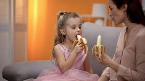 H?rlig liten prinsessa och mamma som ?ter bananer, sunda mellanm?l, n?ring royaltyfria bilder
