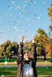 H?rlig lycklig kvinna p? ber?mpartiet med konfettier som ?verallt faller p? henne arkivbilder