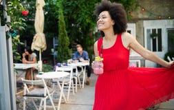 H?rlig lycklig svart kvinna som dricker den sunda drinken och att le arkivbild